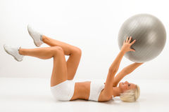 Woman with fitness ball exercise abdominals white Stock Photos