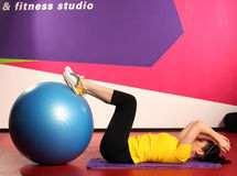 Woman with fitness ball in gym at physical training in sport wear Stock Photos