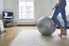 Woman By Fitness Ball Watching Television Royalty Free Stock Image