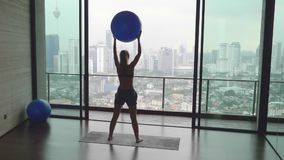 Woman with Fitness Ball. Young happy fit woman doing fitness exercise with fitness-ball in gym with great view over city skyline.Sport,healthy and active stock footage
