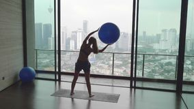 Woman with Fitness Ball. Young happy fit woman doing fitness exercise with fitness-ball in gym with great view over city skyline.Sport,healthy and active stock video