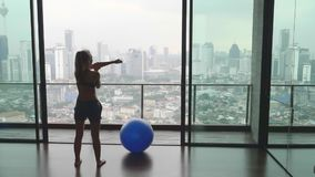 Woman with Fitness Ball. Young happy fit woman warming up before doing fitness exercise with fitness-ball in gym with great view over city skyline.Sport,healthy stock footage