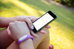 Woman with fitness band on her wrist using her mobile phone. In the park Royalty Free Stock Image
