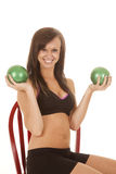 Woman fitness black shorts bra green balls up. A woman with a smile on her face sitting and working with weight balls Stock Image