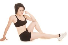 Woman fitness black sports bra sit flex. A woman working out in a black sports bra and shorts Royalty Free Stock Photography