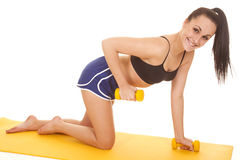Woman fitness blue shorts knees one weight up Royalty Free Stock Images