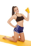 Woman fitness blue shorts knees weights one hand Stock Photo