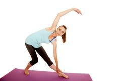 Woman fitness blue tank barefoot straight leg bend Royalty Free Stock Image