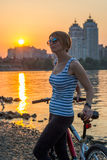 Woman with a fitness bracelet stands and rests after a bike ride Stock Image