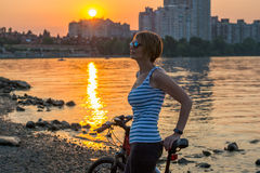 Woman with a fitness bracelet stands and rests after a bike ride Royalty Free Stock Photos