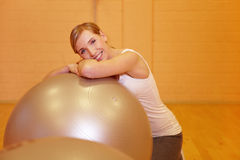 Woman in fitness center on gym ball Stock Photos