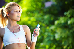 Woman during fitness on city is listen to the music Royalty Free Stock Photography