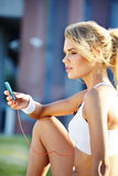 Woman during fitness on city is listen to the music Stock Photo