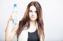 Woman after fitness class proposing a bottle of water Royalty Free Stock Photography