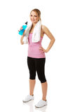 Woman in fitness clothes drinking isotonic drink. Royalty Free Stock Images