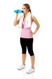 Woman in fitness clothes drinking isotonic drink. Attractive woman in fitness clothes drinking isotonic drink Royalty Free Stock Photos