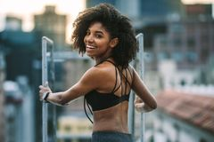 Portrait of female athlete standing on rooftop looking back. Woman in fitness clothes standing on rooftop holding staircase and looking back. Fitness woman royalty free stock photo