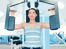 Woman in fitness club. Woman is engaged in fitness club on the simulator Stock Image
