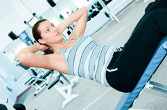 Woman in fitness club. Woman is engaged in fitness club on the simulator Royalty Free Stock Photo
