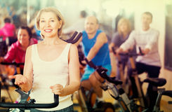 Woman on fitness cycle with people Royalty Free Stock Images