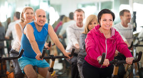 Woman on fitness cycle with  people Stock Images