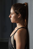 Woman in fitness dress leaning against a wall Stock Photo