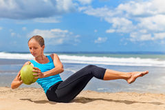 Woman fitness exercise with green coconuts on ocean beach royalty free stock image