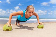 Woman fitness exercise with green coconuts on ocean beach Royalty Free Stock Images