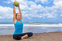 Woman fitness exercise with raw coconut on ocean beach. Woman fitness exercise with raw coconut as weight to keep fit and health. Ocean beach surf background Royalty Free Stock Image