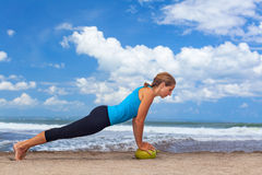 Woman fitness exercise with raw coconut on ocean beach. Woman fitness exercise plank on raw green coconut to keep fit and health. Ocean beach surf background Royalty Free Stock Photography