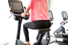 Woman at the fitness gym biking. Woman at sport fitness gym weight training for beauty body. Girl doing indoor biking in a fitness club Royalty Free Stock Photo