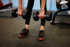 Woman at the fitness gym exercising. Woman at sport fitness gym weight training for beauty body. Fitness girls with dumbbells Royalty Free Stock Photography