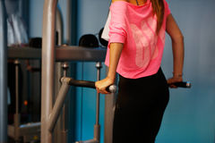 Woman at the fitness gym exercising. Woman at sport fitness gym weight training for beauty body. Fitness girls with dumbbells Stock Images