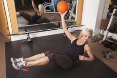 Woman fitness gym hold up ball Royalty Free Stock Images
