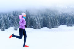 Woman fitness inspiration and motivation, runner. Sport, fitness inspiration and motivation. Young happy woman cross country running in mountains on snow, winter stock image