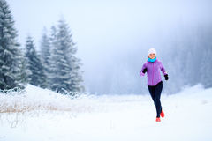 Woman fitness inspiration and motivation, runner. Sport, fitness inspiration and motivation. Young happy woman cross country running in mountains on snow, winter royalty free stock photos