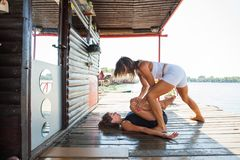Woman fitness instructor assisting young woman in exercise outdo Royalty Free Stock Photography