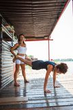 Woman fitness instructor assisting young woman in exercise outdo Stock Images