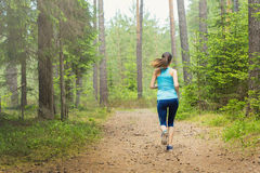 Woman fitness jogging workout in nature, wellness concept. Stock Images