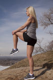 Woman fitness stand rock knee up Royalty Free Stock Photo