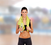Woman in fitness with a towel drinking water Stock Images