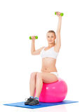 Woman in fitness wear exercising with fitness-ball and dumbbells Stock Photos