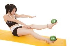 Woman fitness yellow mat balls foot up Stock Image
