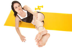 Woman fitness yellow mat lay legs side Stock Photo