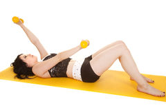 Woman fitness yellow mat lay weights royalty free stock photography