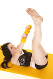 Woman fitness yellow mat weights legs up Royalty Free Stock Images