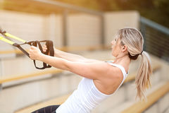 Woman fitness. Young attractive woman doing upper body exercise training arms using trx suspension straps outdoor alone, sun flare Stock Photography