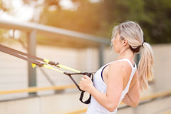 Woman fitness. Young attractive woman doing upper body exercise training arms using trx suspension straps outdoor alone, sun flare Royalty Free Stock Photo
