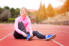 Woman fitness. Young attractive woman tying shoelaces before or after training enjoying time after good workout, sun flare Royalty Free Stock Images