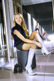 Woman fits on white boots in a boutique Royalty Free Stock Photography